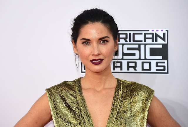 Olivia Munn stands in a green dress at the American Music Awards.