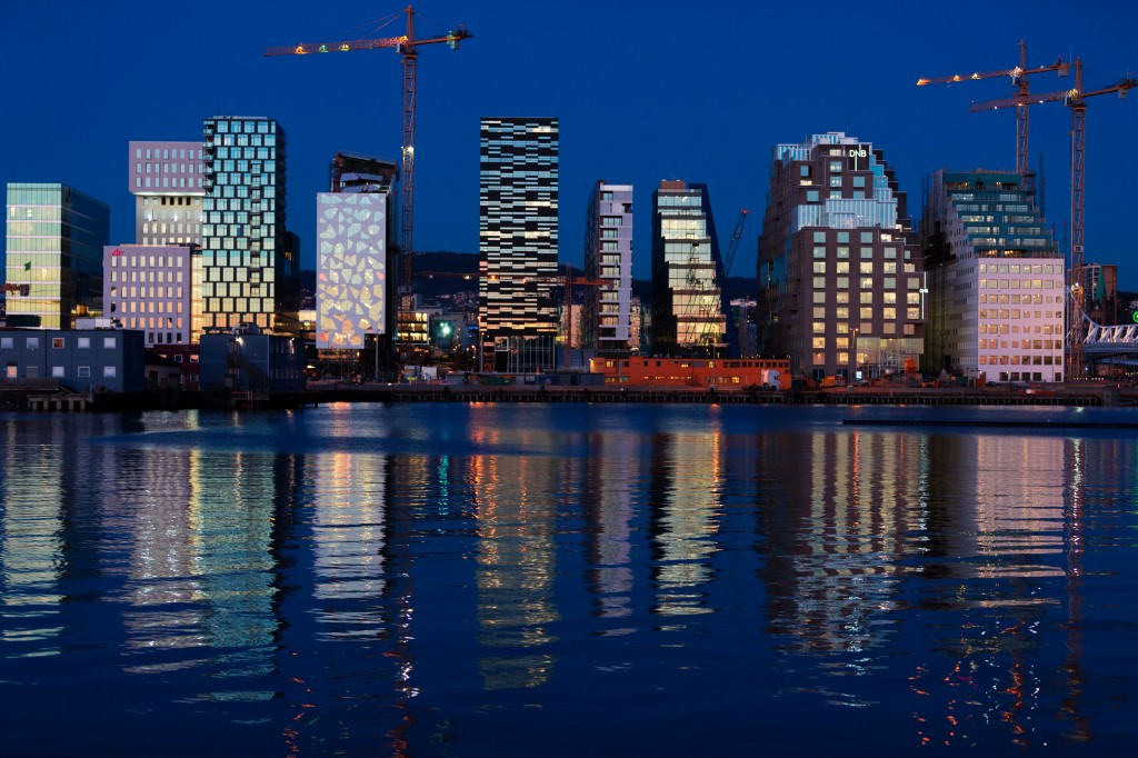 Buildings of The Barcode Project are reflected on the water at sunset in Oslo