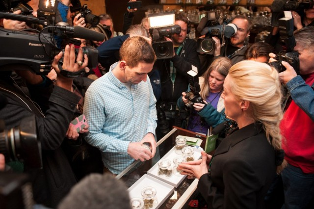 Sean Azzariti, a veteran of the Iraq war, prepares to make the first legal recreational marijuana purchase in Colorado from advocate Betty Aldworth at the 3-D Denver Discrete Dispensary on January 1, 2014 in Denver, Colorado. Legalization of recreational marijuana sales in the state went into effect at 8am this morning. (Photo by Theo Stroomer/Getty Images)