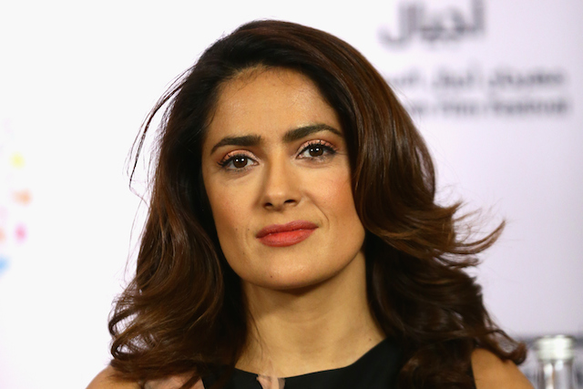 Salma Hayek sits on stage and stares straight ahead at the audience in front of a panel.