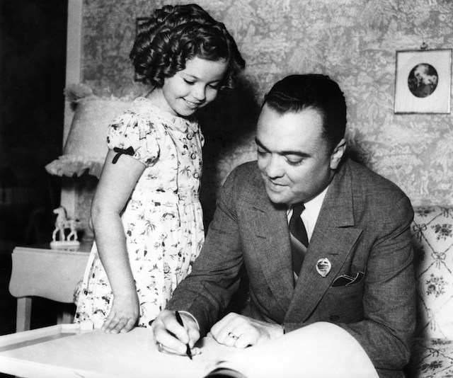 John Edgar Hoover, signing young actress Shirley Temple's autograph books