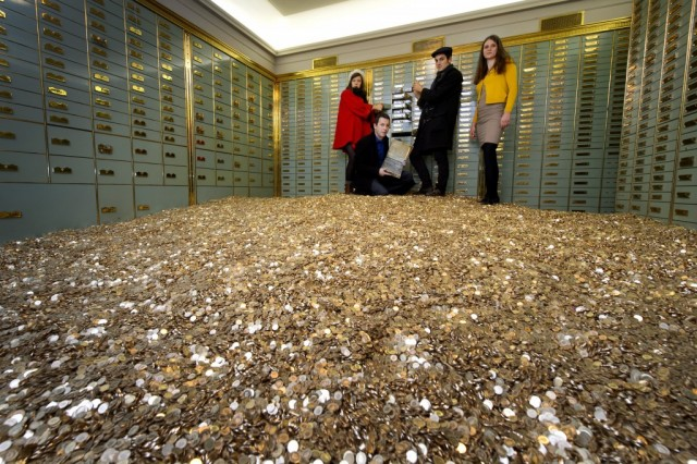 (L to R) Members of 'Generation Basic Income' Marilola Wili, Daniel Haeni, Che Wagner and Pola Rapatt pose with eight million coins of Swiss five-cent in a vault on December 3, 2013 in Basel, inside a bank safe that will both go on sale on a luxury website. The 15 tons coins were dumped by a truck last october in front of the Swiss house of Parliament in a symbolic gesture when the activists submitted over 130,000 signatures to organize a nationwide referendum guaranteeing all Swiss nationals a basic income of CHF 2,500 a month (2,700 USD). (Photo by Fabrice Coffrini/AFP/Getty Images)
