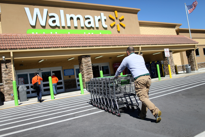 Walmart employee Yurdin Velazquez pushes grocery carts at a Walmart store on February 19, 2015 in Miami, Florida. The Walmart company announced Thursday that it will raise the wages of its store employees to $10 per hour by next February, bringing pay hikes to an estimated 500,000 workers. (Photo by Joe Raedle/Getty Images)