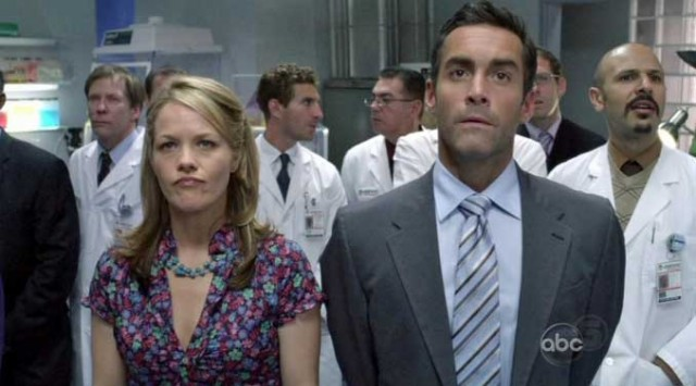 A woman and a man stand in front of a group of men in lab coats in Better Off Ted