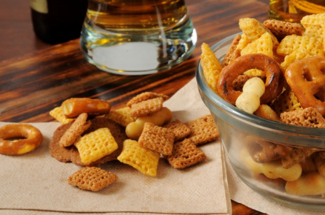 Chex Mix in a bowl and on a table.