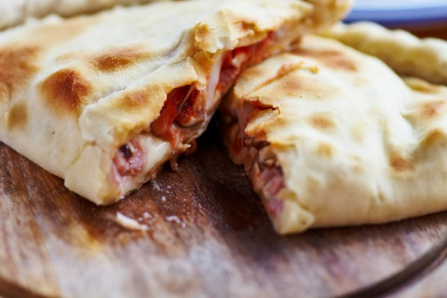 A freshly cut calzone is ready to be served for eating