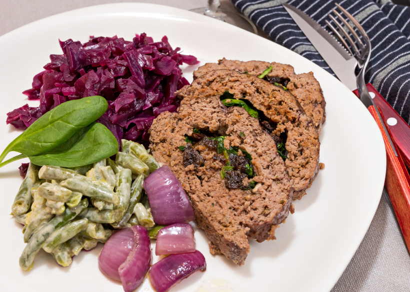 Meatloaf stuffed with spinach and a side dish of red cabbage and green beans
