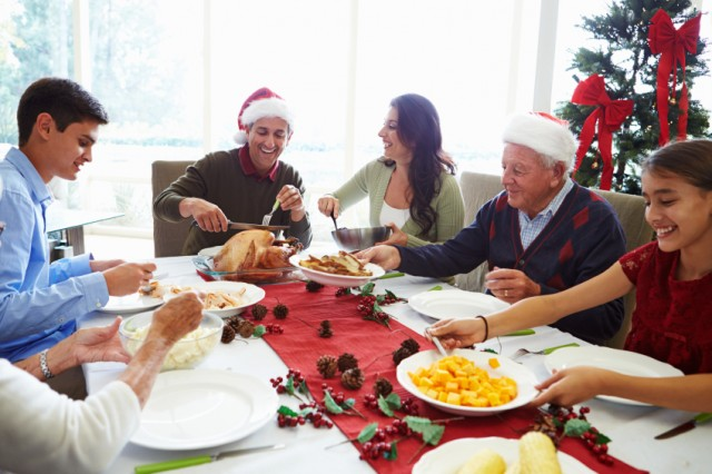 family around the dinner table enjoying a holiday meal