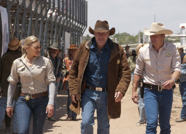 Robert Taylor and Katee Sackhoff walk together sporting sheriff badges in a scene from Longmire
