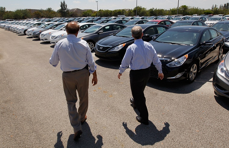 A car salesman shows a customer vehicles
