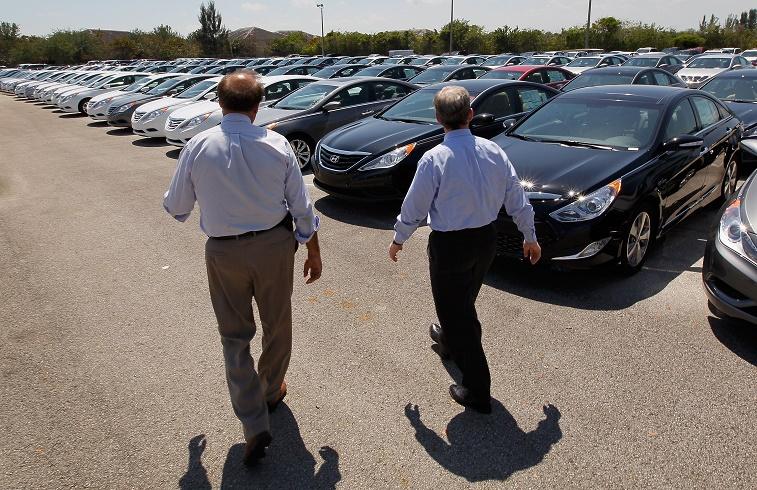 A car salesman shows a client available models