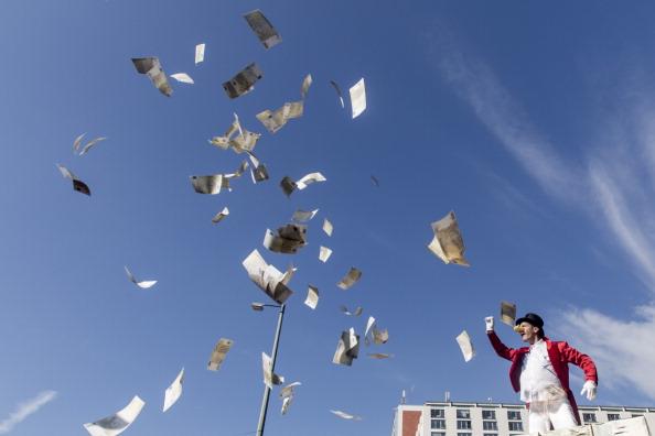 Activist protestors toss money in the air
