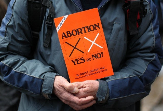 "A person holding an abortion pamphlet in there hands with ""Abortion: Yes or No?"" written on it."