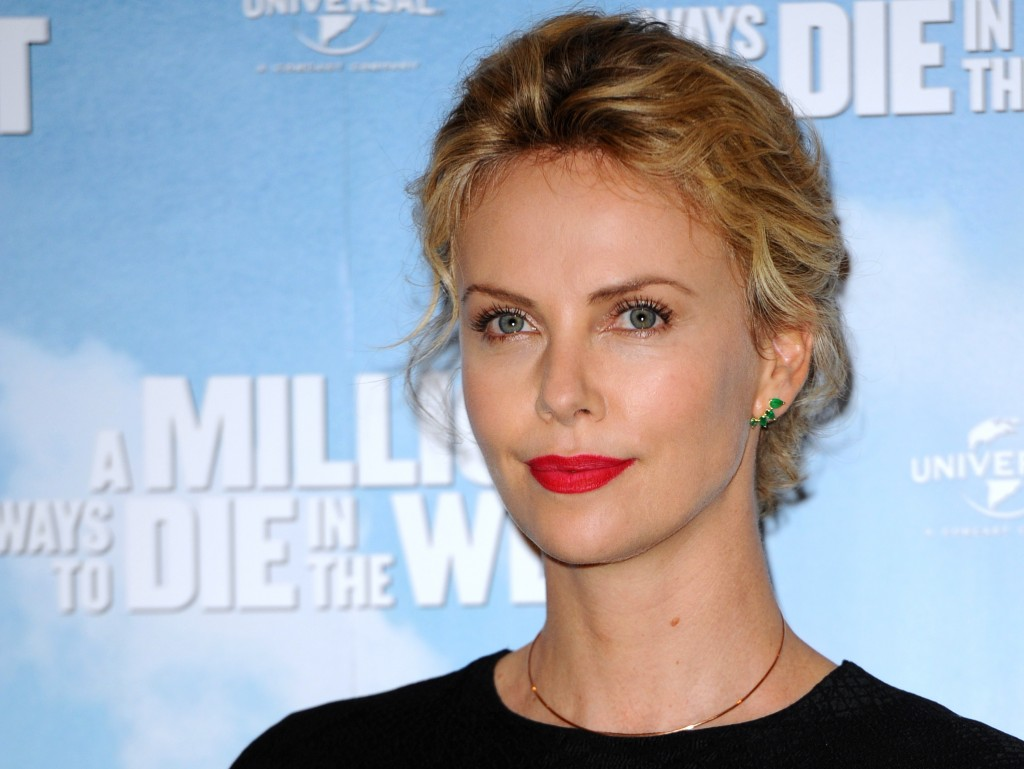 Charlize Theron smiles on the red carpet wearing red lipstick