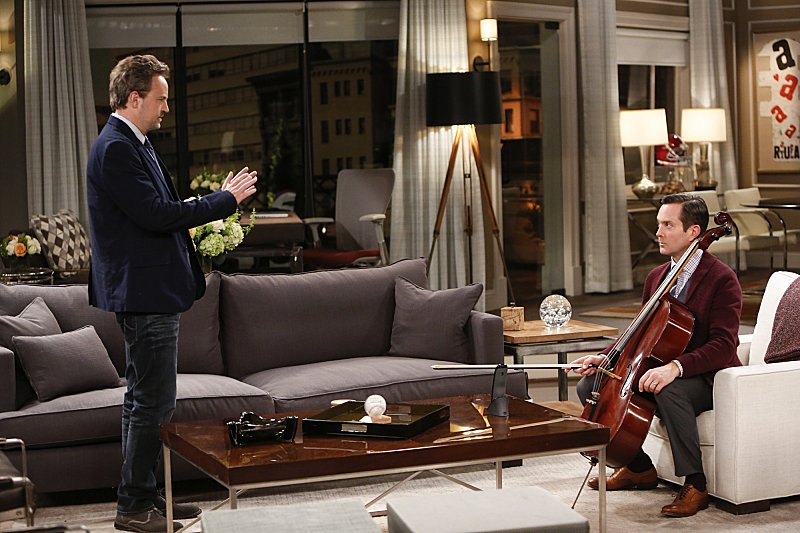 Matthew Perry talks to Thomas Lennon as he plays a cello in a scene from The Odd Couple