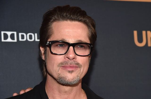 Brad Pitt stands wearing a black shirt and dark rimmed glasses.