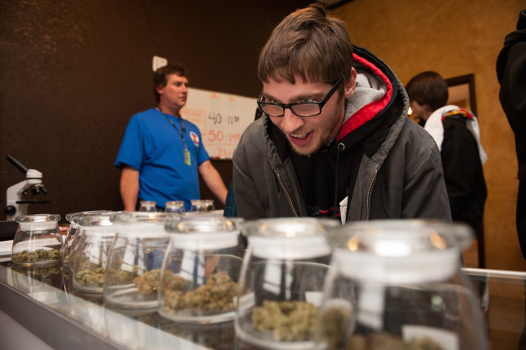 Tyler Williams of Blanchester, Ohio selects marijuana strains to purchase at the 3-D Denver Discrete Dispensary on January 1, 2014 in Denver, Colorado. Legalization of recreational marijuana sales in the state went into effect at 8am this morning. (Photo by Theo Stroomer/Getty Images)