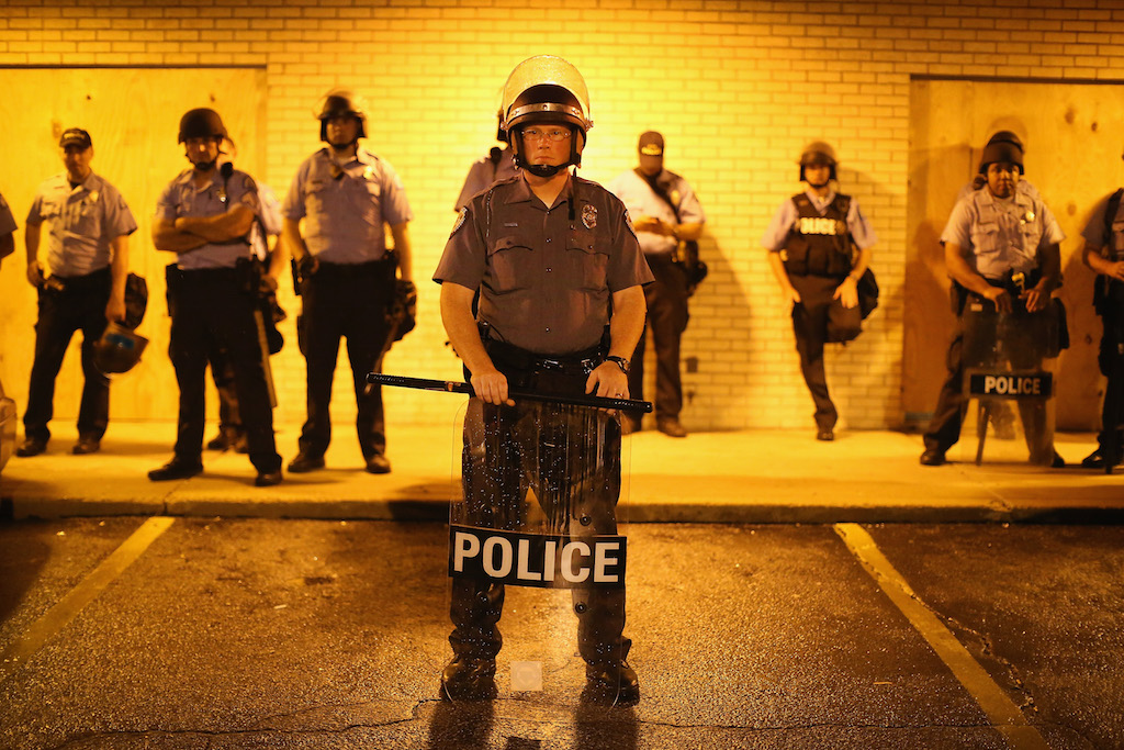 Police stand guard before the mandatory midnight curfew on August 16, 2014 in Ferguson, Missouri. The curfew was imposed on Saturday in an attempt to reign in the violence that has erupted nearly every night in the suburban St. Louis town since the shooting death of teenager Michael Brown by a Ferguson police officer on August 9. (Photo by Scott Olson/Getty Images)