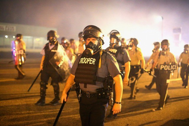 Police advance through a cloud of tear gas toward demonstrators protesting the killing of teenager Michael Brown on August 17, 2014 in Ferguson, Missouri. Police shot smoke and tear gas into the crowd of several hundred as they advanced near the police command center which has been set up in a shopping mall parking lot. Brown was shot and killed by a Ferguson police officer on August 9. Despite the Brown family's continued call for peaceful demonstrations, violent protests have erupted nearly every night in Ferguson since his death. (Photo by Scott Olson/Getty Images)