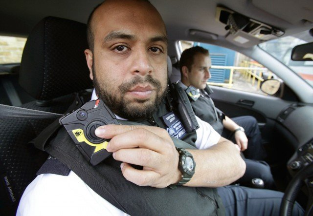 Constable Yasa Amerat (left) and Constable Craig Pearson pictured in their police car wearing body-worn video (BWV) cameras, ahead of a year-long pilot scheme by the Metropolitan police, at Kentish Town on May 6, 2014 in London, England. Officers with the Metropolitan Police will be begin wearing tiny cameras on their uniform, designed to capture evidence at scenes of crime and help support prosecution cases. The trial, thought to be the largest in the world, will see a total of 500 cameras distributed to 10 London boroughs. (Photo by Yui Mok - WPA Pool/Getty Images)