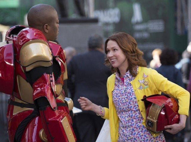 Titus Burgess dressed as a Transformer talking to Ellie Kemper who is holding his helmet in 'Unbreakable Kimmy Schmidt'