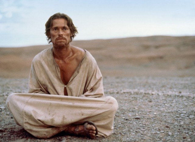 Willem Dafoe as Jesus sitting on the ground wearing sandals and a cloth robe in the desert in The Last Temptation of Christ