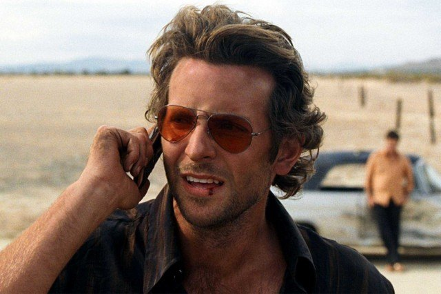 Bradley Cooper holds a phone to his ear while standing in the desert in a scene from The Hangover