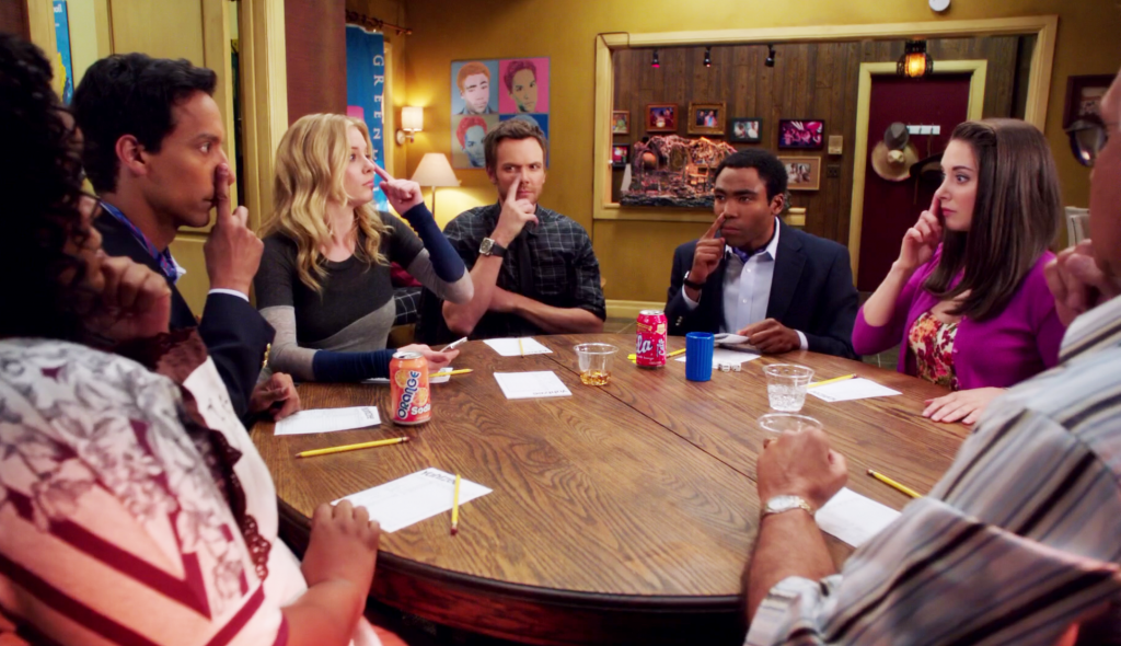 Yvette Nicole Brown as Shirley Bennett, Danny Pudi as Abed Nadir, Gillian Jacobs as Britta Perry, Joel McHale as Jeff Winger, Donald Glover as Troy Barnes, Alison Brie as Annie Edison, and Chevy Chase as Pierce Hawthorne sitting at a table with paper, pencils, and drinks with their fingers on their noses in a classroom on Community