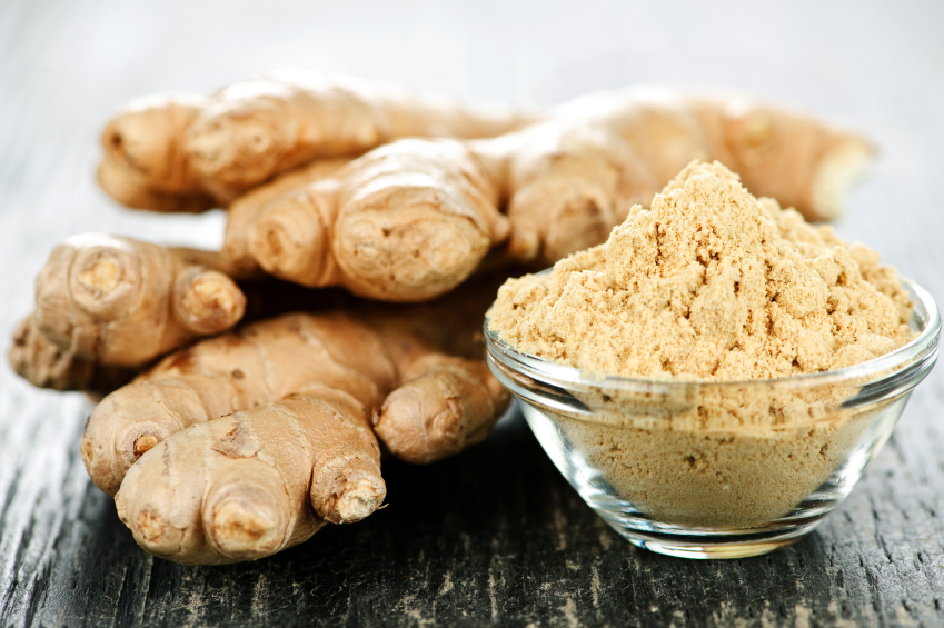 fresh ginger root with small bowl of dried, ground ginger