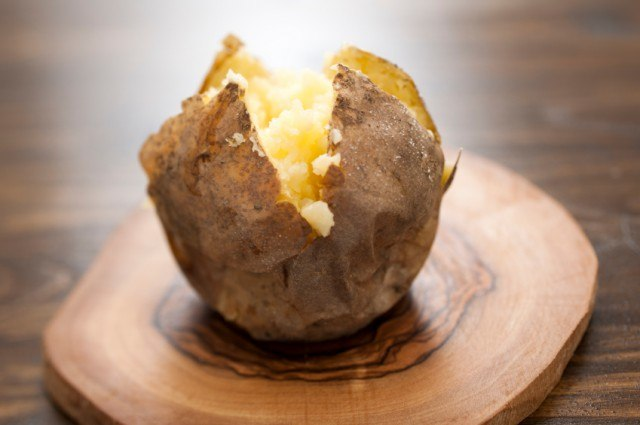 A baked potato on a wooden board.
