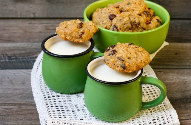pile of oatmeal raisin cookies with two mugs of milk