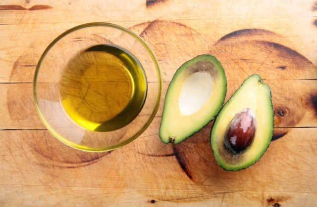 An avocado next to oil