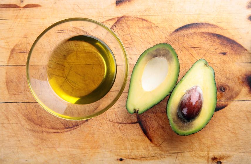 Avocado oil with an avocado cut in half