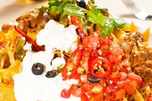 nachos covered in toppings and sour cream