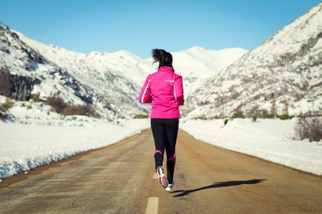 A woman dressed in a pink shirt and black leggings jogs on the road during the winter