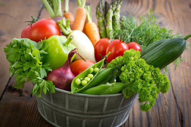 Bucket of vegetables on a wooden table.