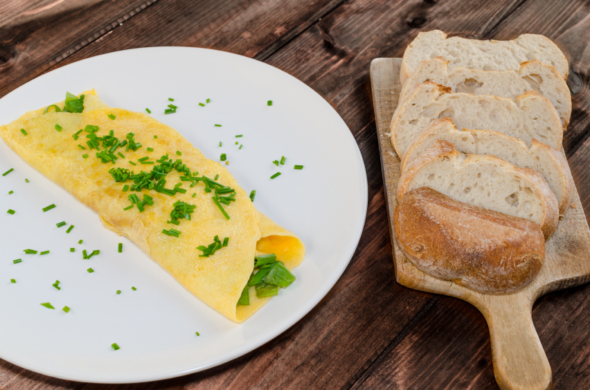 omelet with chives and a loaf of bread