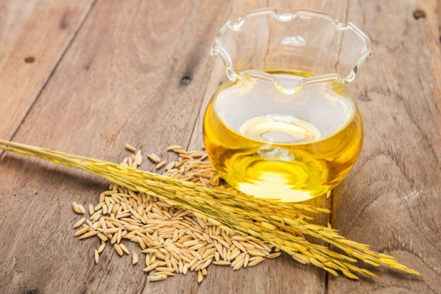 Rice bran oil in bottle glass and unmilled rice on wooden backgr