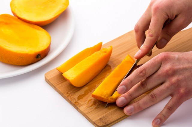Mango Slice Being Cut Into Four Fruit Chips