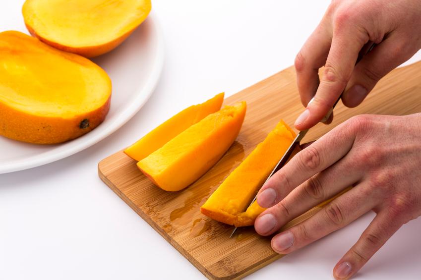 Mango being sliced on a cutting board