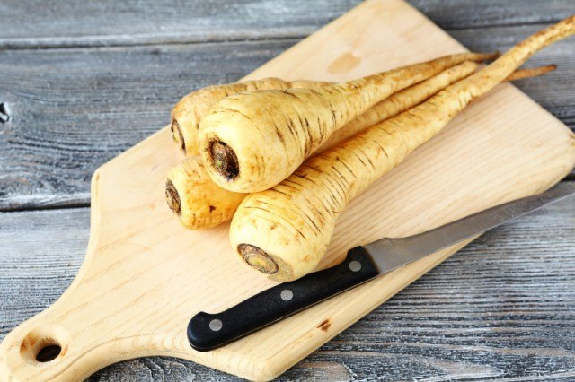 raw parsnips on cutting board with knife
