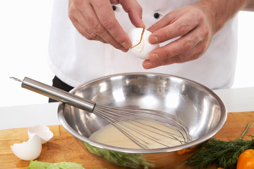 person cracking egg into bowl