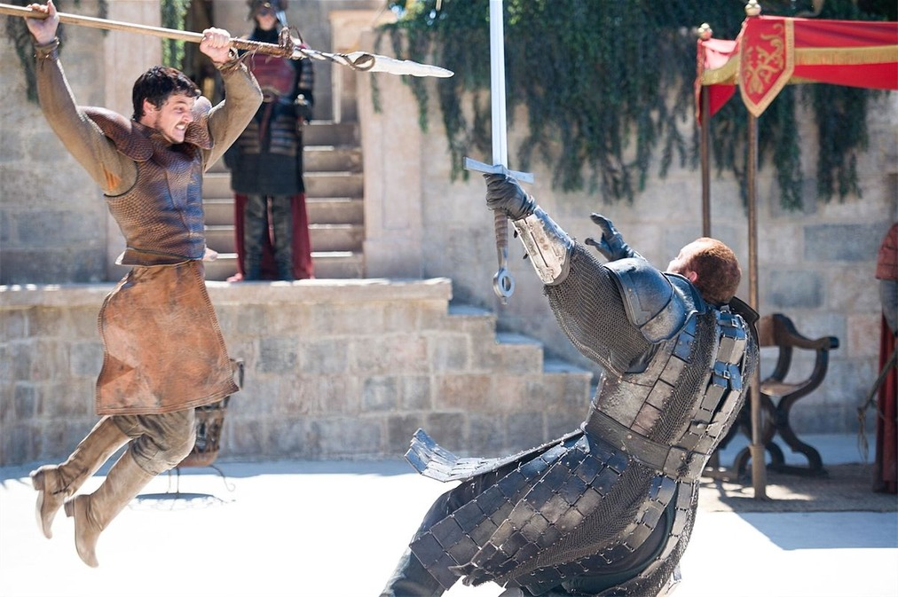 Oberyn Martell with spear in hand, jumps at a full armored Gregor Clegane, who's falling backwards to the ground