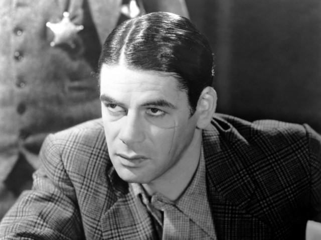 Paul Muni as Tony Capote in a suit with a man wearing a sheriff's badge behind him in Scarface (1932) in black and white
