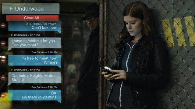 Zoe Barnes is staring at her phone while being watched by a man in disguise.