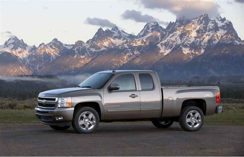 A 2011 Chevy Silverado sits parked in front of picturesque mountains
