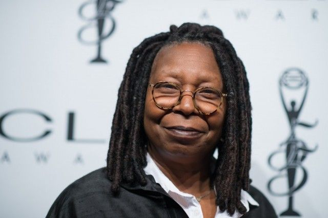 Whoopi Goldberg smiling while wearing a black and white outfit.
