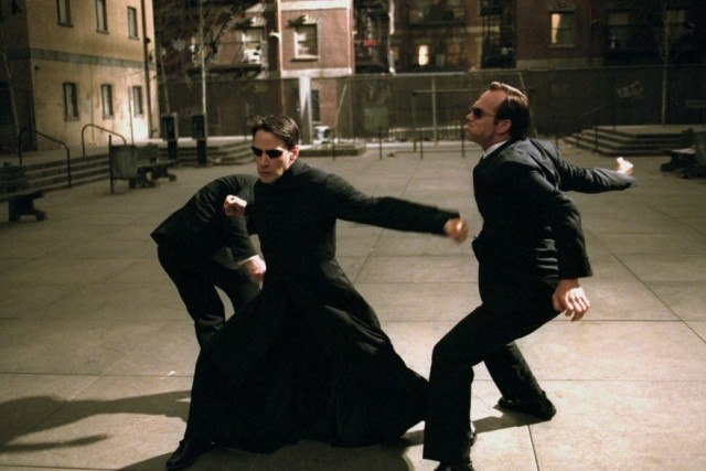 Keanu Reeves' Neo fights two men in suits in a scene from The Matrix Reloaded