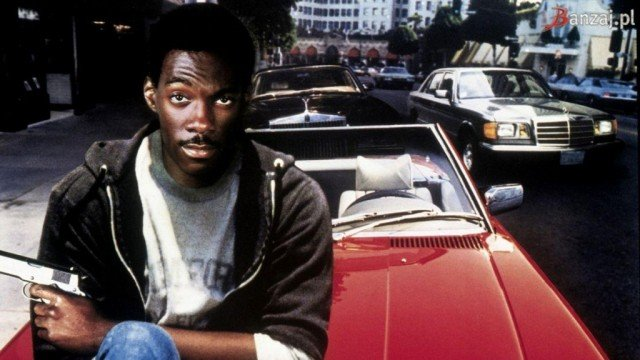 Eddie Murphy sits on the hood of a red car holding a gun in Beverly Hills Cop