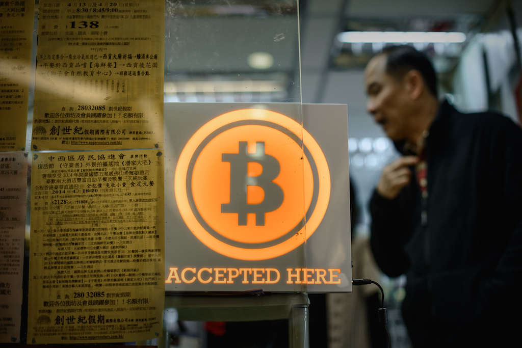 A man walks out of a shop displaying a bitcoin sign during the opening ceremony of the first bitcoin retail shop in Hong Kong on February 28, 2014. Bitcoin was invented in the wake of the global financial crisis by a mysterious computer guru using the pseudonym Satoshi Nakamoto and unlike other currencies, it does not have the backing of a central bank or government. Photo by Philippe Lopez/AFP/Getty Images